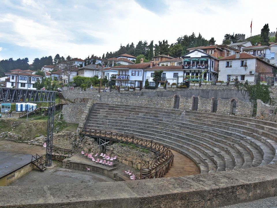 Ancient theater with stage on t he center and houses around it