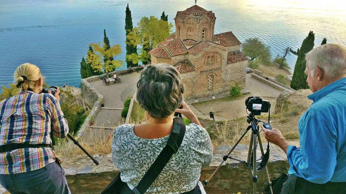 Three people taking picture of the church St. John Keneo and Ohrid lake