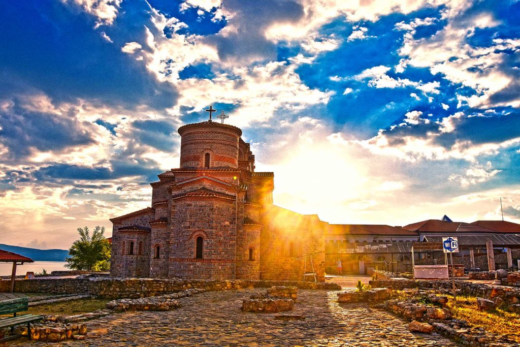 Sun rays and church St.Clement in Ohrid with blue sky and clouds