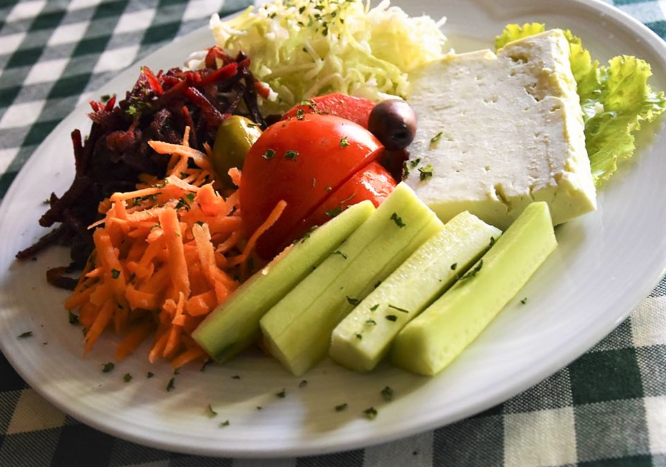 Cucumber, tomato, olives, carrot and cheese in a white plate