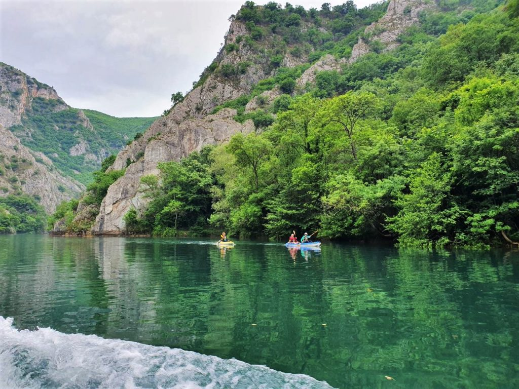 Two kayaks in Matka canyon, high rocks and trees