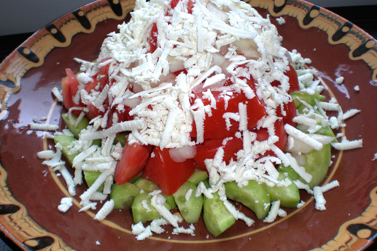 Shopska salad, made from chopped tomatoes, cucumbers, green peppers, onions and grated cheese on top
