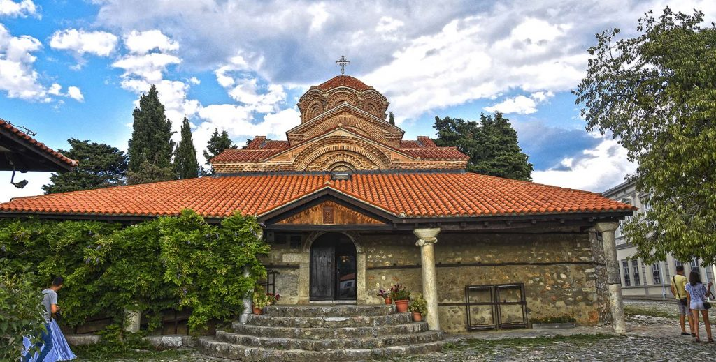 Church dedicated to Mother of God with red roof and blue sky with clouds in the back