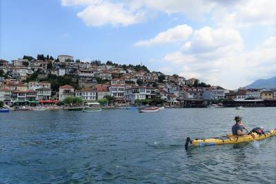 Man kayaking in Ohrid lake with small boats and Ohrid in the background.