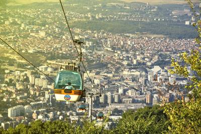 Cable car above green forest with view of Skopje in the front