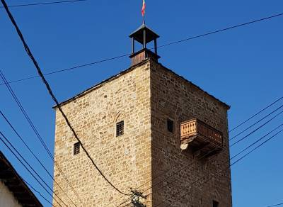 Tower with small windows and one balcony and flag on the top
