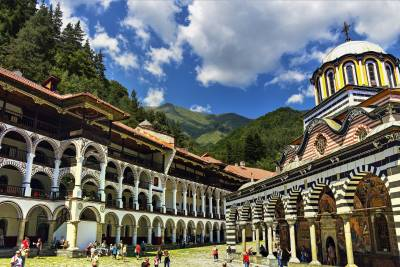 Rila monastery and monastery complex of buildings around, with mountains with pine forest and blue sky with clouds in the background.