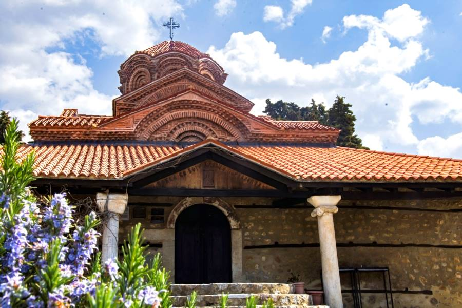 The Holy Mother of God – Peribleptos in Ohrid with blue flowers infront and clouds and blue sky in the background