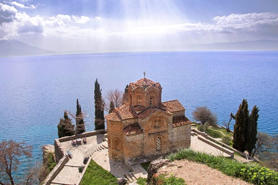 Saint John the Theologian Kaneo wit sunrays and Ohrid lake on the background