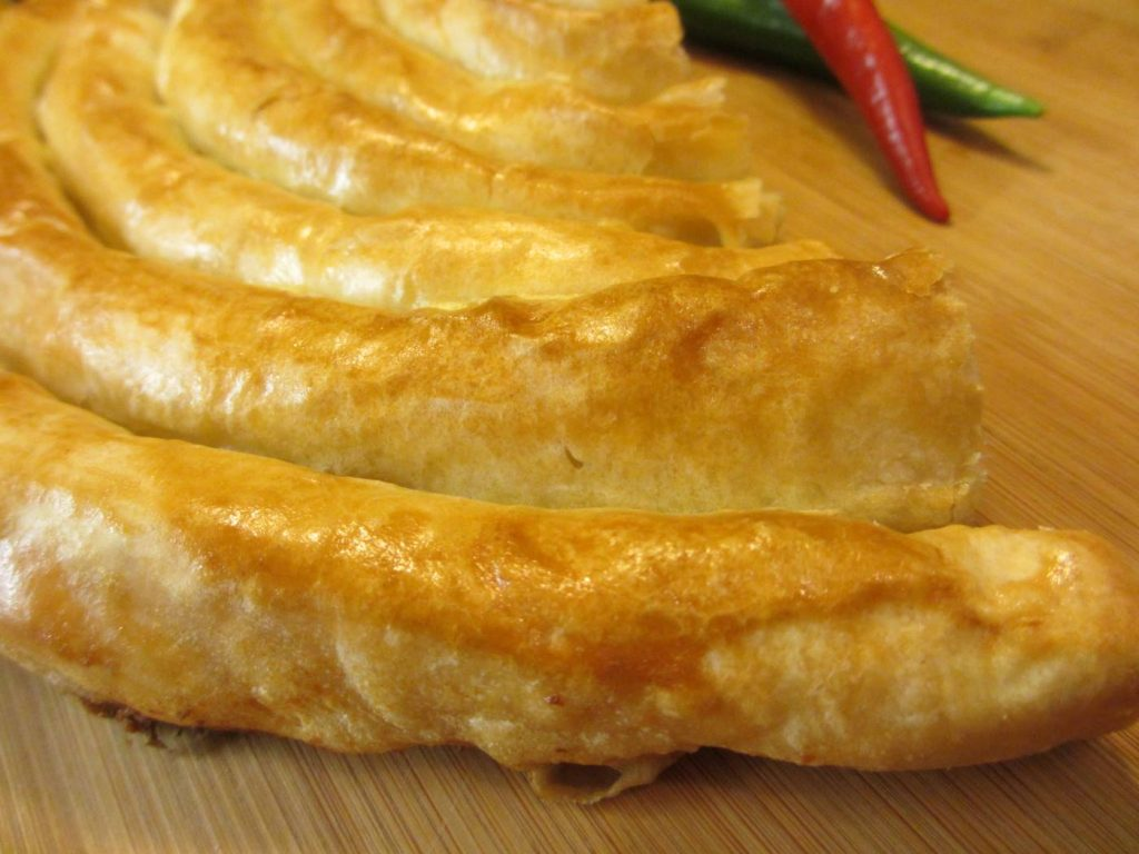 Traditional Macedonian pastry on a wooden table together with one red and one green pepper.